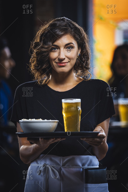 Portrait of mid adult waitress carrying food and drink on serving tray in bar