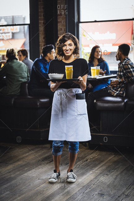 Portrait of waitress carrying food and drink on serving tray in bar