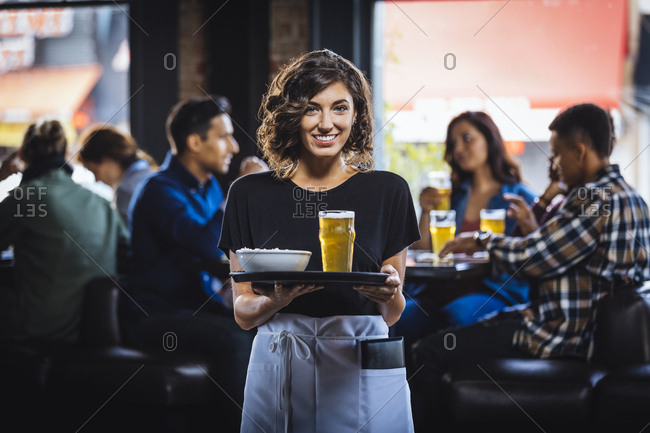 Portrait of smiling waitress carrying food and drink on serving tray in bar