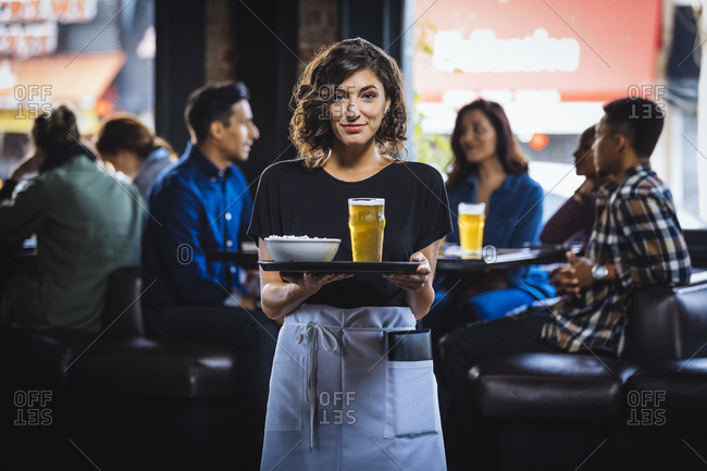 Portrait of beautiful waitress carrying food and drink on serving tray in bar