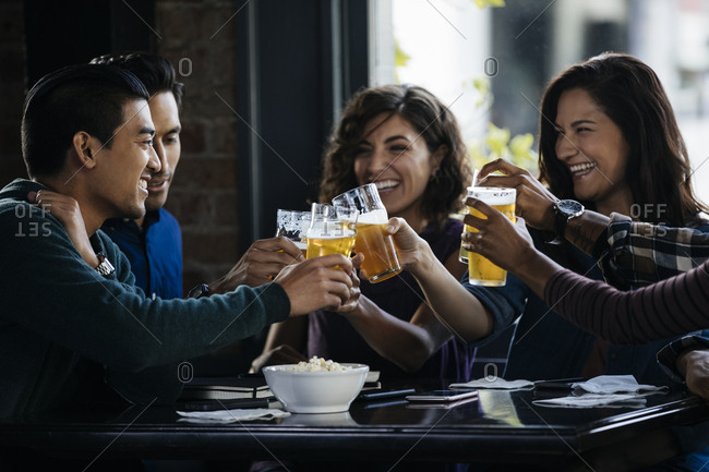 Group of multiethnic friends toasting beer glasses at table in bar