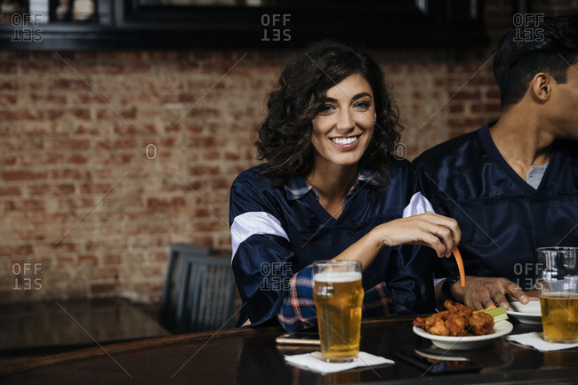 Portrait of mid adult woman eating and drinking in sports bar