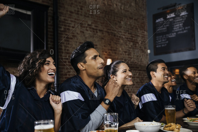 Group of friends watching sports on TV at bar