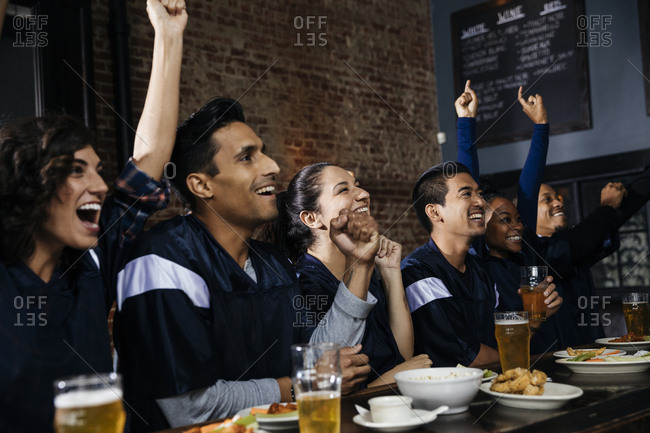 Group of friends cheering while watching sports on TV at bar