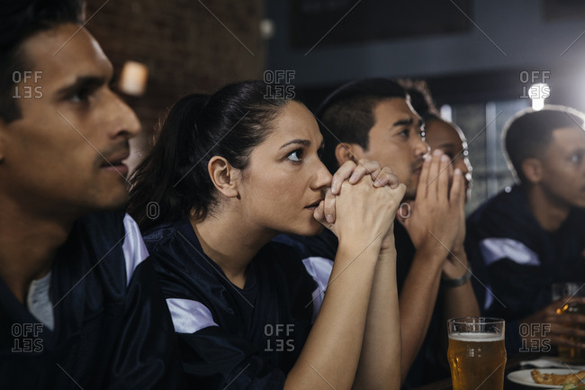 Serious male and female friends with hands clasped watching football game in bar