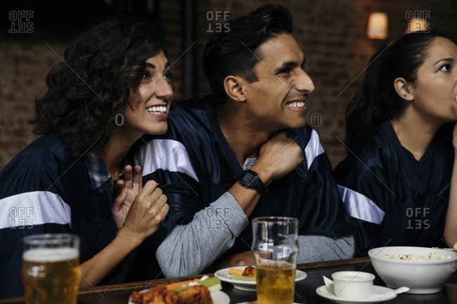 Happy man and woman watching sports on TV at bar