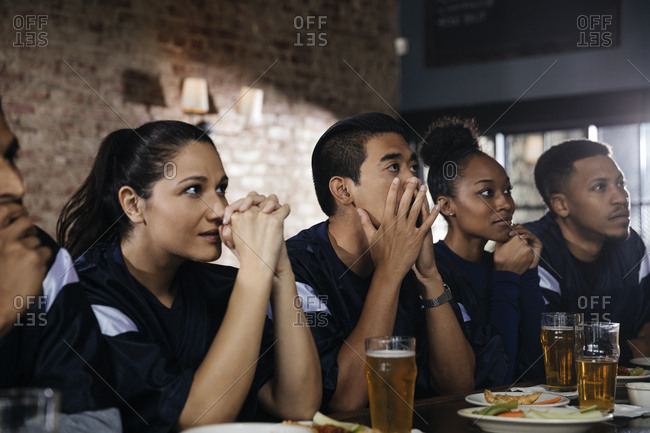 Sports fans watching TV at bar in pub
