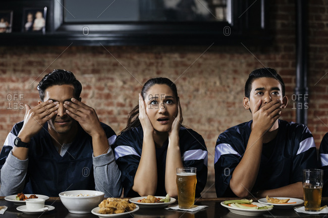 Multiethnic friends showing symbol of three wise monkeys while watching soccer match at bar counter