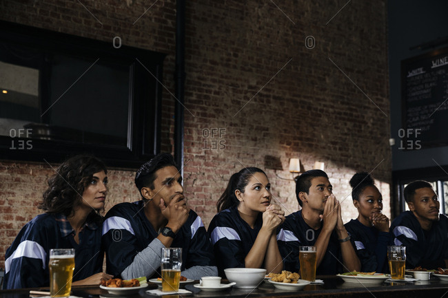 Group of serious friends watching sports on TV at bar counter