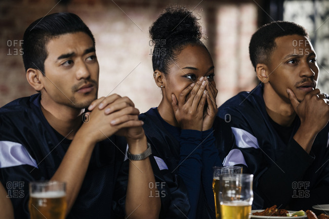 Young woman covering face while watching sports with male friends in bar