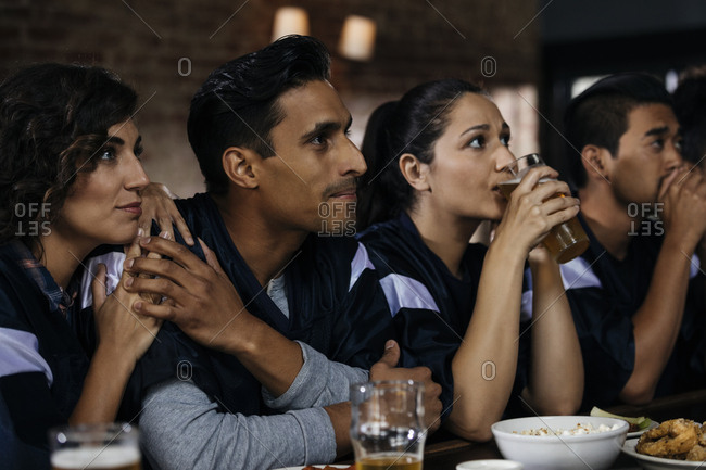Multiethnic friends watching soccer match together in bar