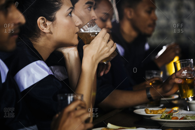 Woman drinking beer while watching sports on TV with friends in bar