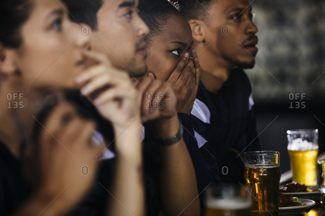 Serious young woman covering face while watching soccer match with friends in bar