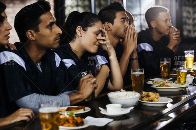 Disappointed woman sitting by friends watching sports on TV at bar in pub