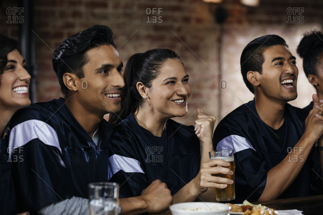 Happy multiethnic friends celebrating goal at counter in bar