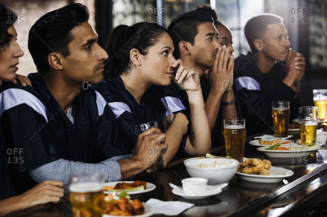 Serious male and female friends wearing t-shirts while watching soccer match together at bar counter