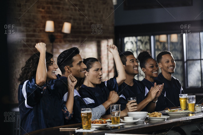 Happy male and female sports fans celebrating while watching TV at bar