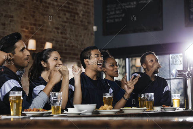 Happy sports fans watching TV at bar in pub