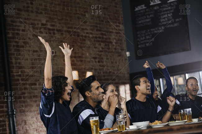 Group of sports fan celebrating victory at bar in pub