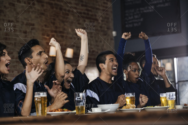 Multiethnic male and female friends screaming while watching soccer match in bar