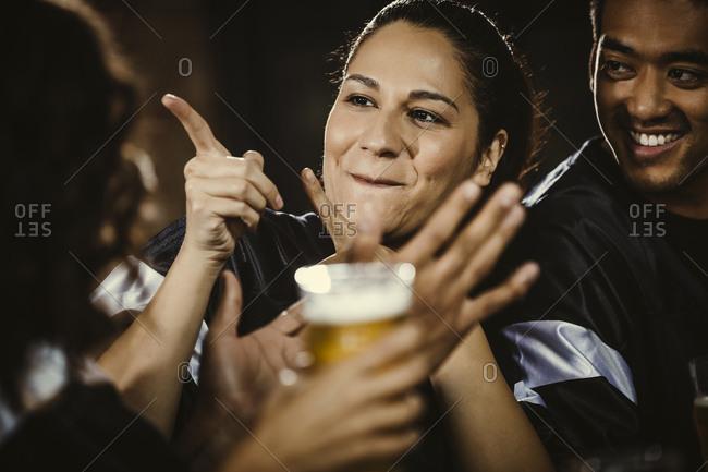 Happy female fan gesturing while looking away in bar