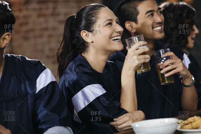 Happy  woman holding beer glass while watching sports on TV with friend in bar