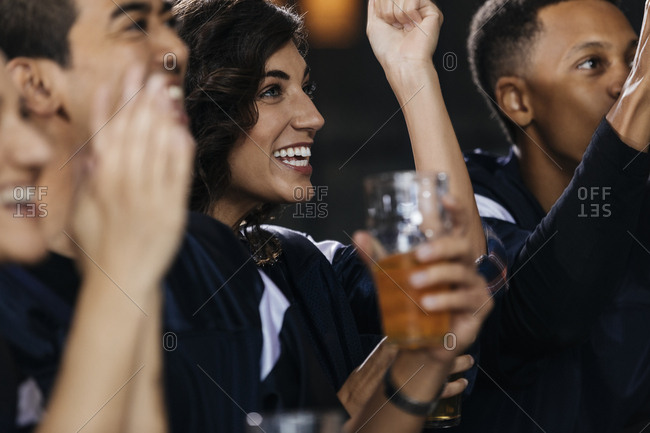 Happy mid adult woman cheering while watching soccer match with friends in bar