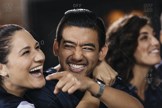 Happy mid adult woman embracing man while watching soccer match in bar