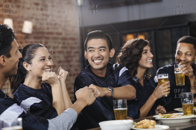Smiling men giving fist bump while watching sports on TV with friends at bar