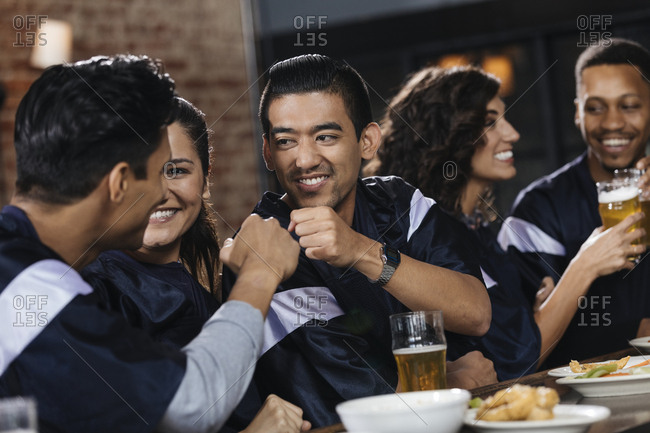 Group of friends giving fist bump while watching sports match with friends at counter in bar