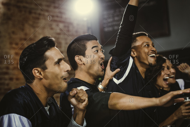 Excited group of friends screaming while watching soccer match at bar