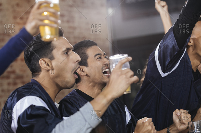 Excited multiethnic male friends screaming at TV in pub