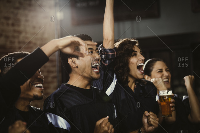 Sports fans celebrating in bar at pub