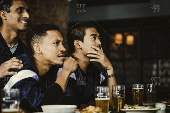 Sports fans watching football on TV in bar