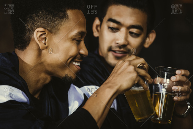 Sports fans toasting beer glasses in bar