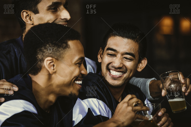 Multiethnic male soccer fans toasting beer glasses in bar