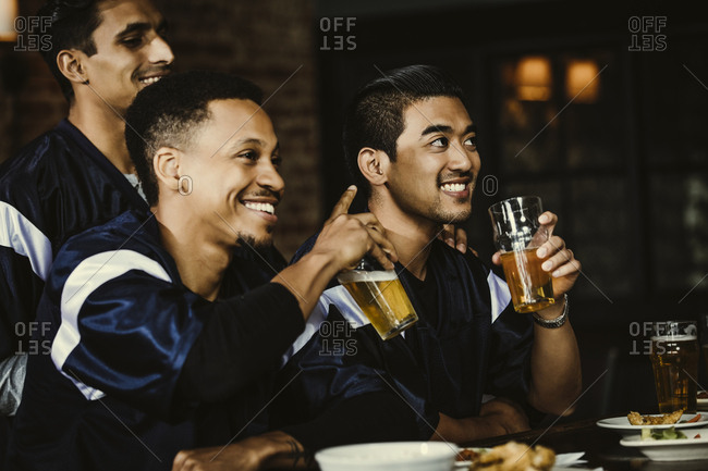 Friends drinking beer while watching Sports on TV in bar