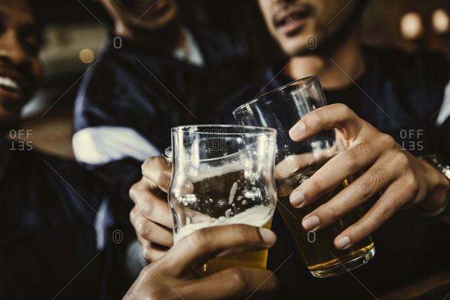 Cropped image of male soccer fans toasting beer glasses in bar