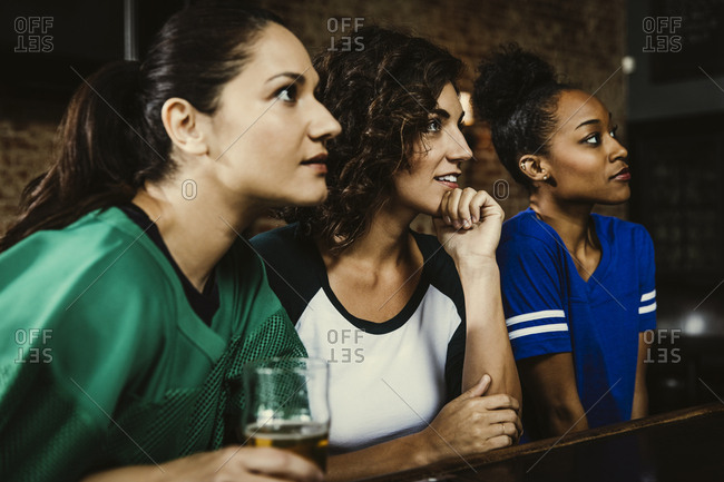 Female fans watching sports on TV at bar in pub