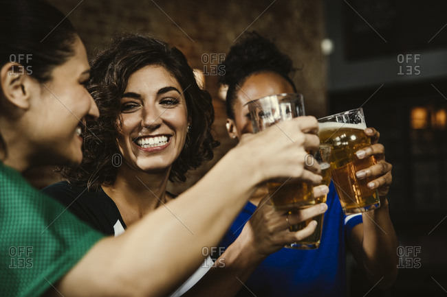 Happy female sports fans toasting beer glasses while watching sports on TV in bar