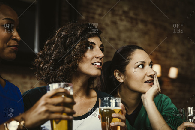 Multiethnic female fans holding beer glasses while watching soccer match in bar