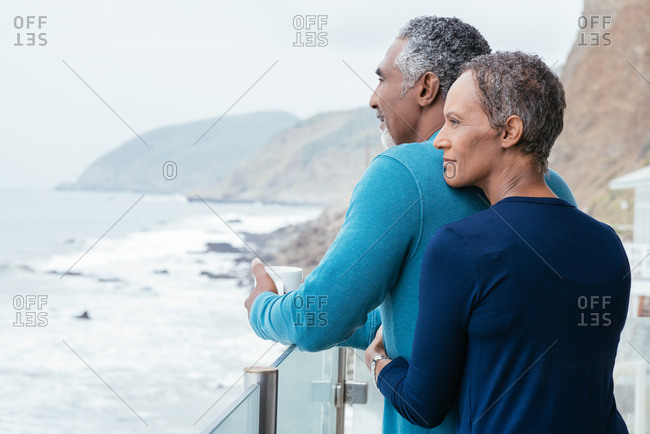 Rear view of mature woman embracing man looking at sea from balcony