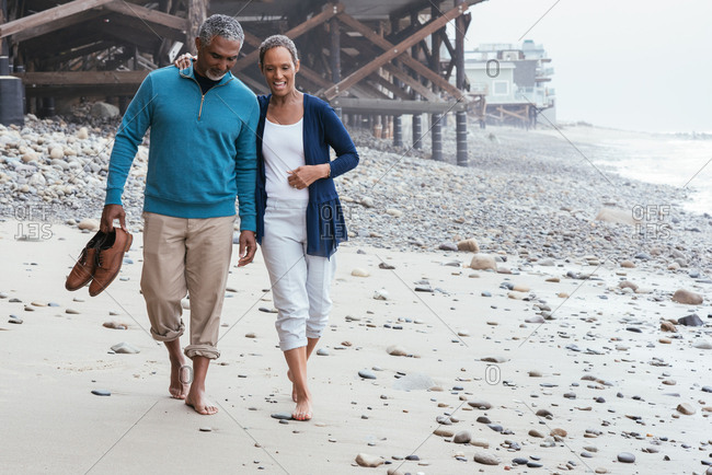 Mature couple walking on rocky beach