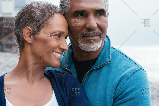 Mature woman smiling while looking at husband at beach