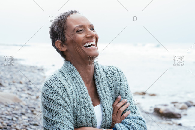 Mature woman laughing while looking away at beach