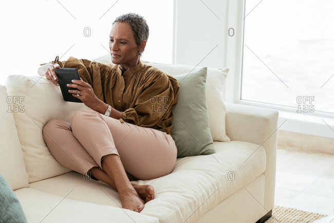Mature woman using tablet computer while sitting on sofa at home