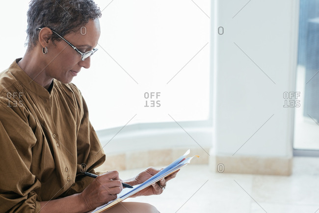 Mature woman with paperwork in home office