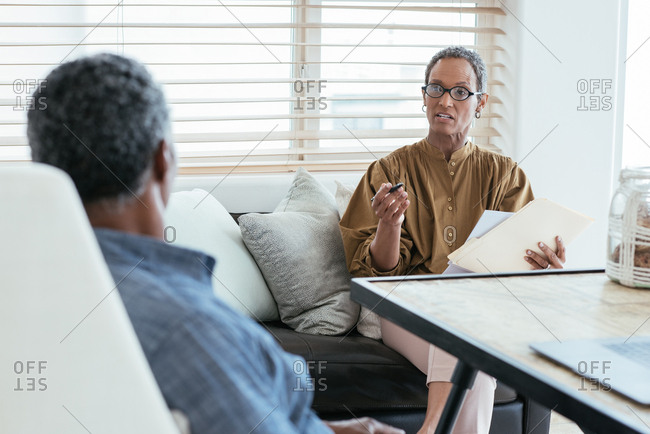 Mature woman holding papers and pen while discussing home finance with husband
