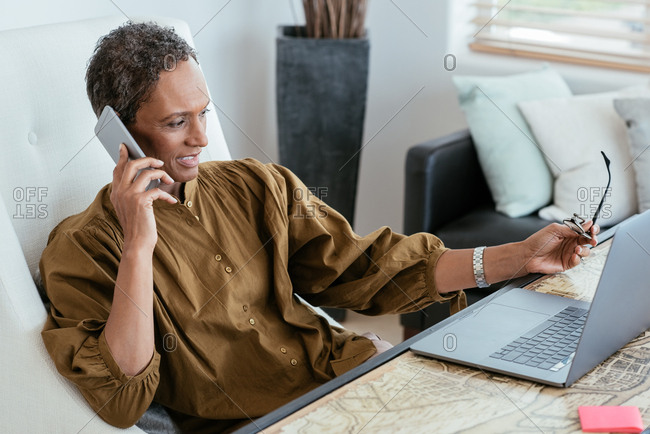 Mature woman using mobile phone while holding eyeglasses in home office