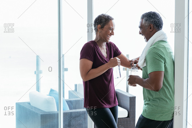 Cheerful fit mature couple talking while holding water bottles at home